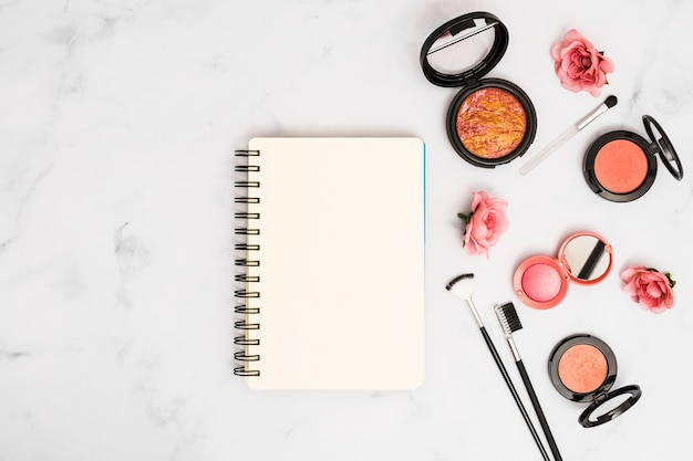 Blank spiral notebook with pink roses; makeup brushes and compact powder