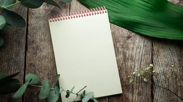 Пустой спиральный блокнот с местом для текста на деревянном фоне с листьями растений и веточкой эвкалипта, вид сверху плоская планировка