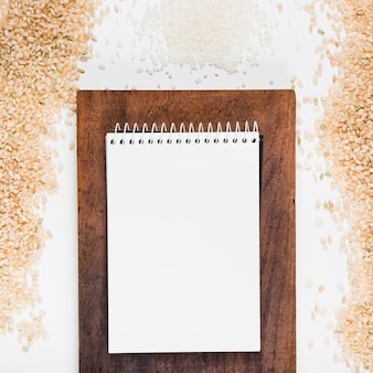 Blank spiral notepad on chopping board with brown and white rice on white background