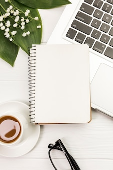 Blank spiral notepad on laptop and coffee cup with leaves and flowers on desk