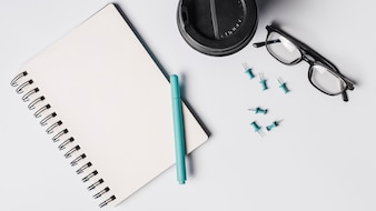 Blank spiral notepad; pen; coffee cup; eyeglasses and pushpins on white background