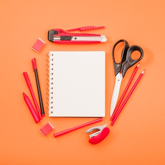 Blank spiral notepad and scissor with stationery over bright orange background