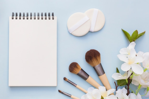 Blank spiral notepad; sponge and makeup brush with white flowers on blue backdrop