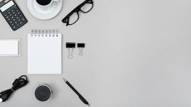 Blank spiral notepad surrounded with calculator; tea cup; paper clip; speaker; pen; cable and eye glasses over grey background