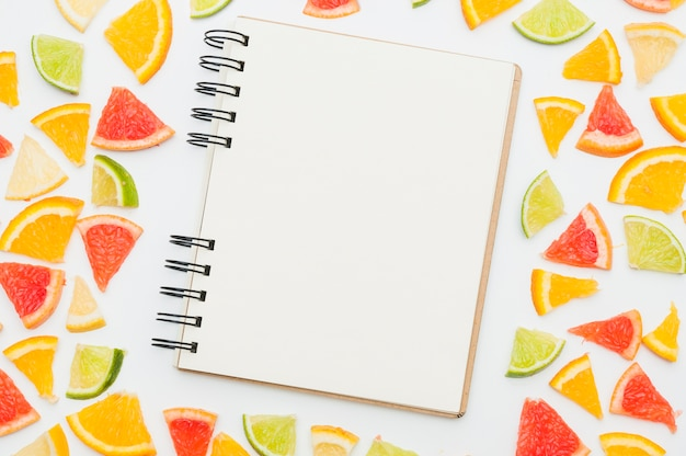 Blank spiral notepad surrounded with citrus fruit slices on white backdrop