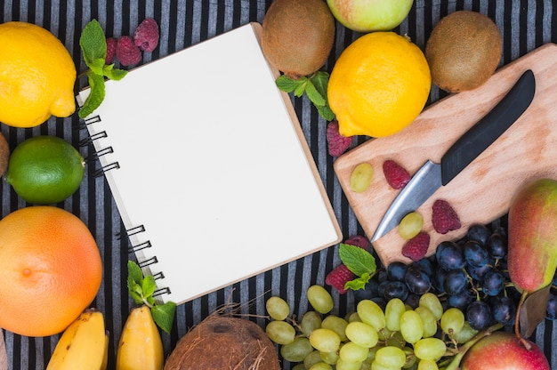 Blank spiral notepad surrounded with colorful fruit and knife on chopping board