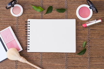 Blank spiral notepad surrounded with cosmetics products on placemat