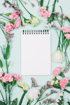 Blank spiral notepad surrounded with limonium; carnations and eustoma flowers against blue background