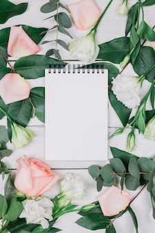 Blank spiral notepad surrounded with pink rose and flowers on wooden desk