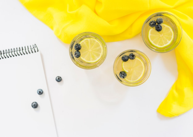 Blank spiral notepad with glasses of lemon juice on white backdrop