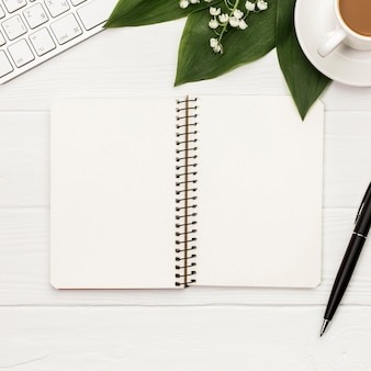 Blank spiral notepad with keyboard,coffee cup and pen on white backdrop