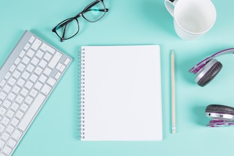 Blank spiral notepad with keyboard; eyeglasses; cup; headphone and pencil on turquoise background