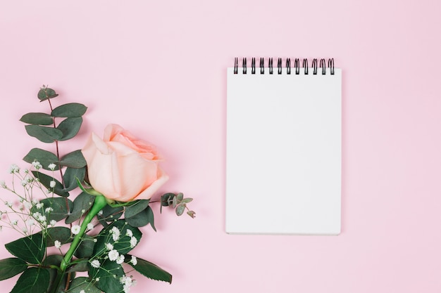 Blank spiral notepad with rose and gypsophila flower against pink background
