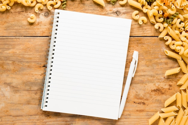 Blank spiral notepad with variety of raw pasta over table