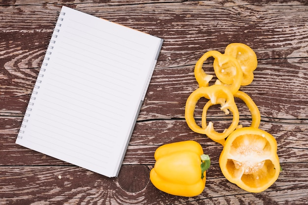 Blank spiral notepad with whole and slices of yellow bell pepper on wooden desk