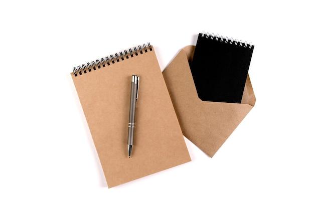 흰색 배경에 자동 펜 옆에 쌓인 빈 나선형 메모장과 재활용 봉투. 교육, 사무실, 환경 보호, 폐기물 제로.