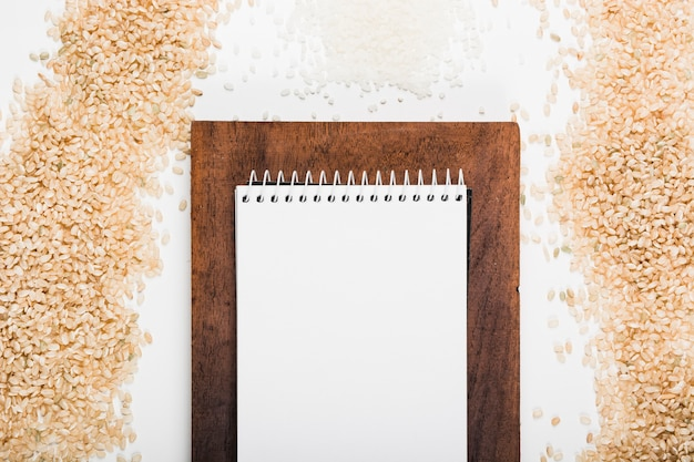 Blank spiral white notepad over the brown wooden board with uncooked rice on white background