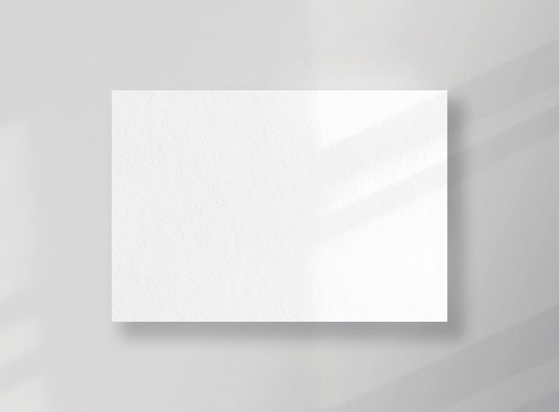 Blank square card, sheet as mockup with sunny shadows on gray surface