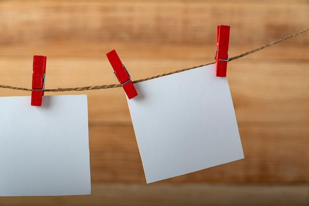 Blank square note paper card hanging with wooden clip or clothespin on rope string peg. copy space.