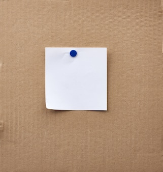 Blank square white sheet of paper attached with an iron button
