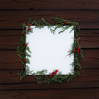 Blank square with christmas pine leaves around on rustic wooden background
