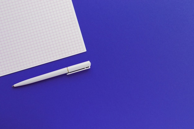 Blank squared paper and pen on trendy blue background. for ideas message, list and inspiration. top view, flat lay with copy space. mockup for your design.