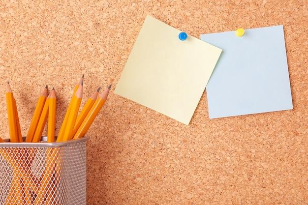 Пустые наклейки, прикрепленные к пробковой доске, и желтые карандаши в пенале
