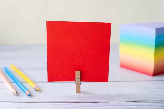 Пустая записка со стопкой зажима для стирки красочной бумажной ручки, помещенной на стол, пустой кусок