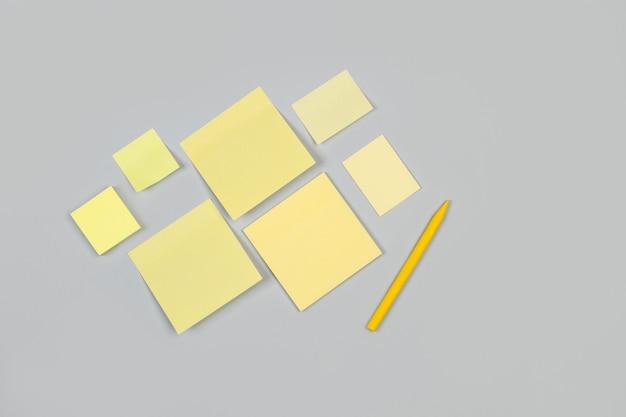 空白の付箋と灰色の背景に黄色のクレヨン