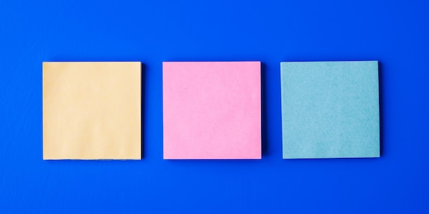 Blank sticky notes on a light blue background. top view
