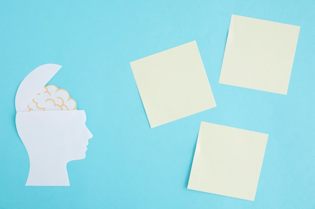 Blank sticky notes with brain in the open head on blue background