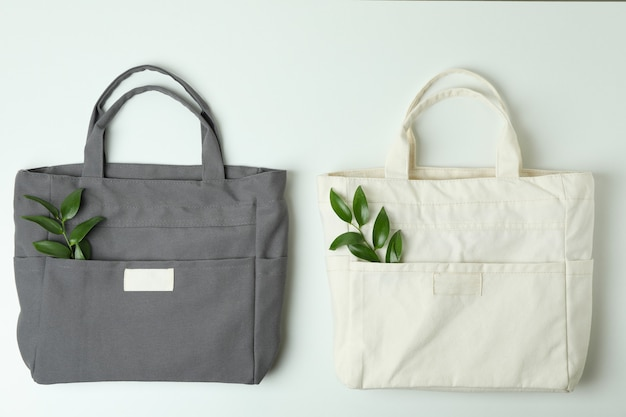 Blank stylish eco bags with twigs on white surface