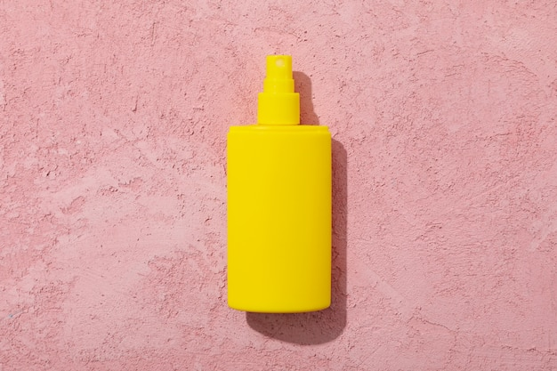 Blank sunscreen bottle on pink surface