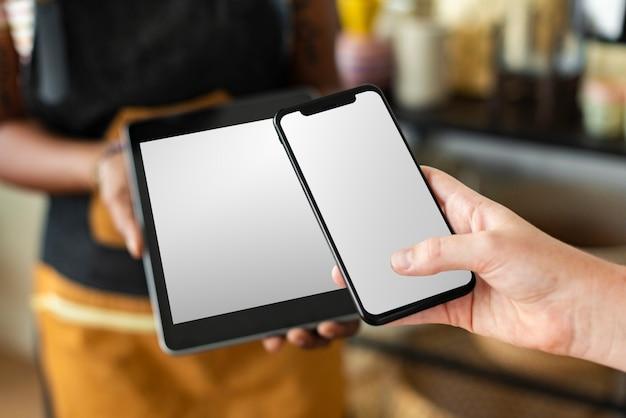 中小企業の店で空白のタブレットとスマートフォンの画面