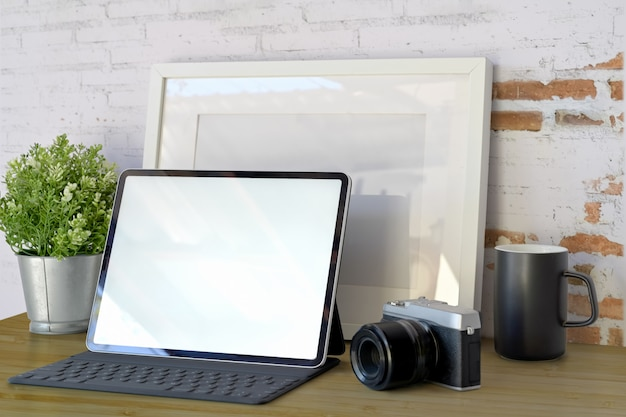 Blank tablet computer screen on workplace in front on old white brick wall with copy space