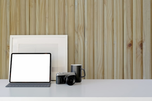 Blank tablet computer screen on workplace in front on wooden wall with copy space
