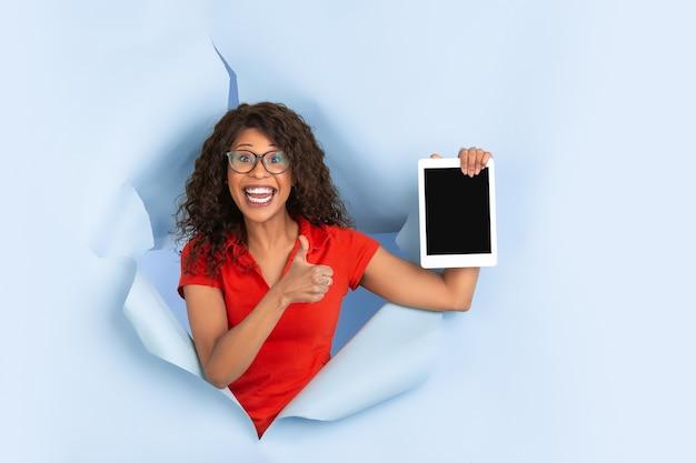 空白のタブレット画面。引き裂かれた青い紙の背景、感情的、表現力豊かな陽気なアフリカ系アメリカ人の女性。突破、突破口。人間の感情、顔の表情、販売、広告の概念。