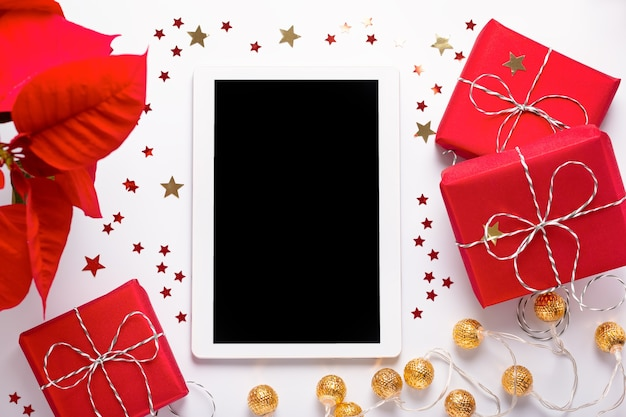 빈 태블릿 화면, 빨간색 선물 상자, 포인세티아 꽃, 흰색의 황금색 크리스마스 조명, 위쪽 전망, 평평한 평지