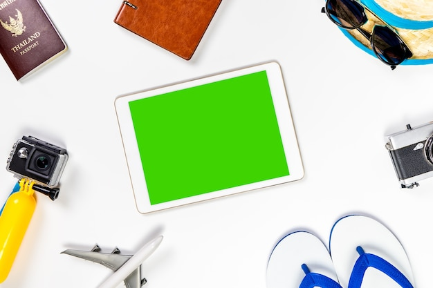 Blank tablet screen surrounded by travel accessories and gadget