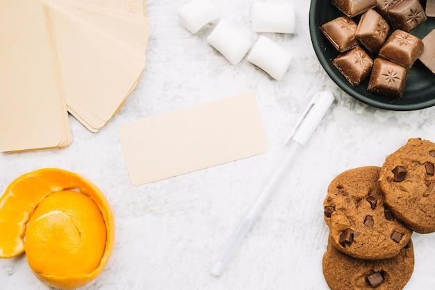 Пустая бирка с шоколадными кусками; зефир; ручка; печенье и апельсиновая корка