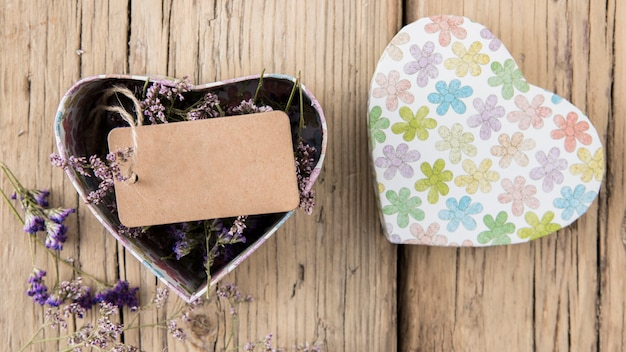 Blank tag with flowers in box in heart shape
