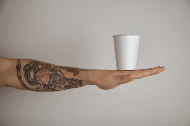 Vuoto da asporto bicchiere di carta sulla mano dell'uomo brutale tatuato, presentazione vista laterale isolato su priorità bassa bianca