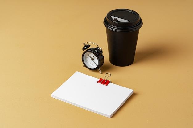 空白のテイクアウトのコーヒーカップと白い名刺