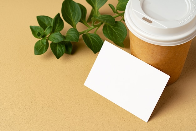 Blank takeaway coffee cup and white businesscards