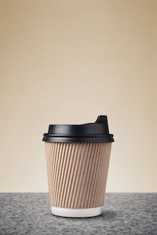 Blank takeaway paper coffee cup with black caps on marble surface against beige wall.