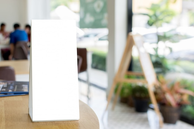 Blank template menu frame on wood table in restaurant with blurred background