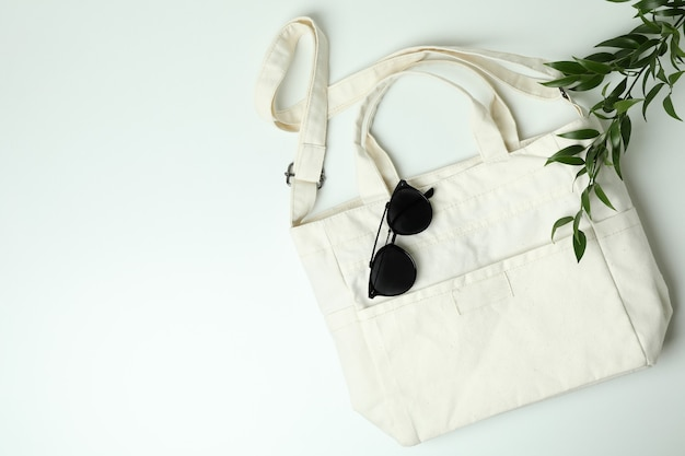 Blank textile bag, branch and sunglasses on white background