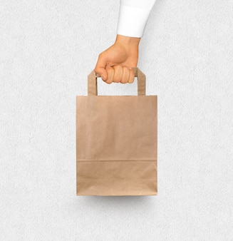 Blank textured paper bag mock up holding in hand isolated near white wall.