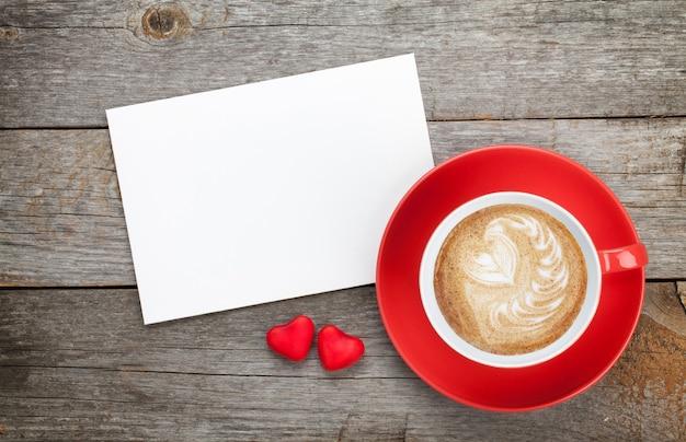 빈 발렌타인 인사말 카드와 나무 배경에 빨간 커피 컵