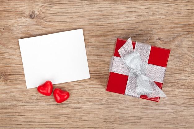 빈 발렌타인 인사말 카드와 나무 배경에 작은 빨간색 선물 상자